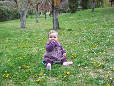 Niña de alrededor de un año sentada sobre la hierba