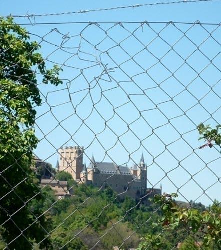 El alcázar de Segovia visto a través de una alambrada