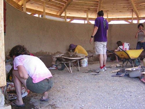 Voluntarios trabajando en la construcción del edificio en una ecoaldea