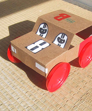 Cochecito de juguete hecho con cartón y tapones de botella