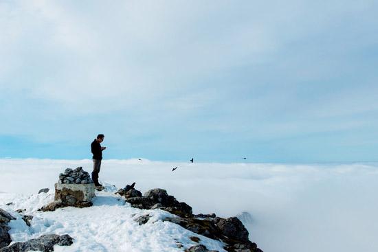 Un hombre en la cima de una montaña solitaria leyendo un Whatsapp