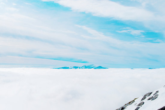 La cima de una montaña solitaria emerge sobre las nubes