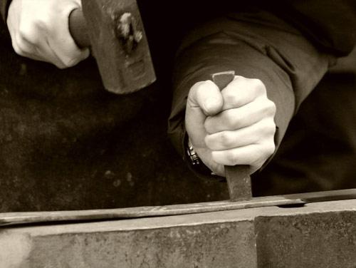 Las manos de un hombre golpeando con un martillo una cuña metálica