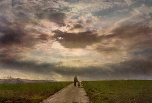 Un anciano y un niño caminan de la mano por un camino hacia un horizonte nuboso